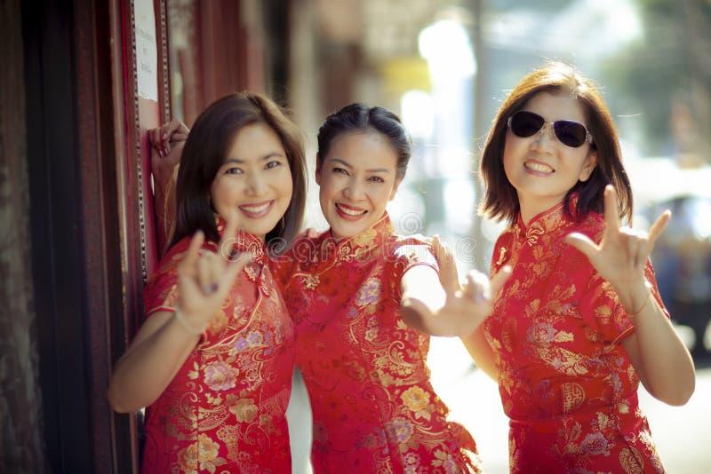 Grupo de mulher asiática que veste a emoção da felicidade da cara da roupa chinesa da tradição e o sinal de sorriso toothy da mão imagens de stock royalty free
