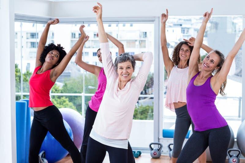 Grupo de mulheres alegres que exercitam com os braços aumentados fotos de stock royalty free