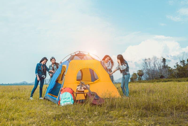 Grupo de mulheres asiáticas novas que ajudam a construção uma barraca para o resto no acampamento do rio do lago fotografia de stock