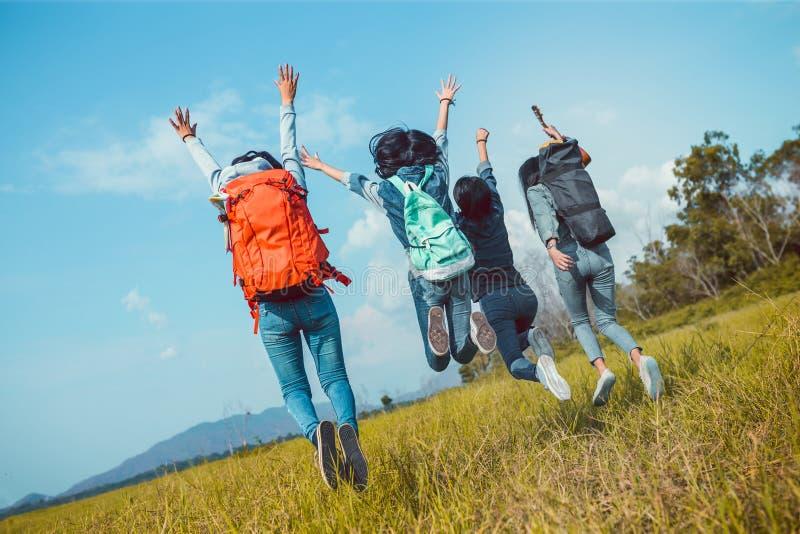 Grupo de mulheres asiáticas novas que saltam para apreciar o curso que trekking imagens de stock royalty free