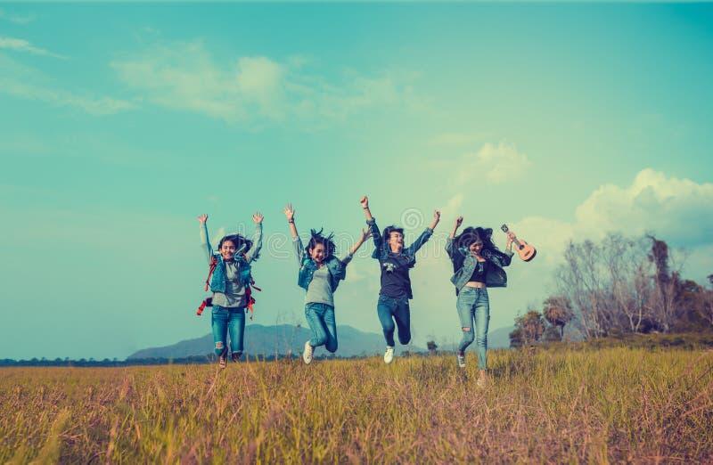 Grupo de mulheres asiáticas novas que saltam para apreciar o curso que trekking foto de stock