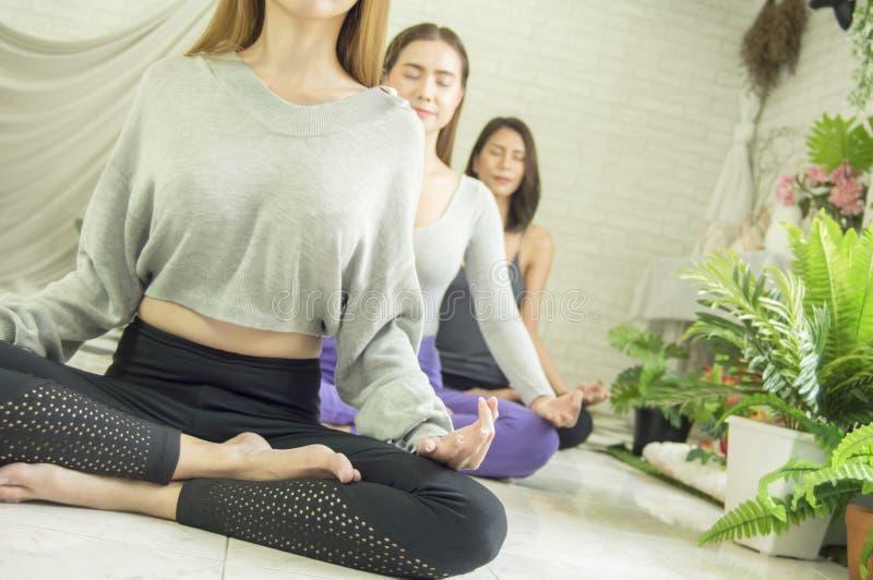 Grupo de mulheres bonitas nas classes da ioga e da meditação para refrescar a mente e o espírito, com conceito do abrandamento e  fotos de stock
