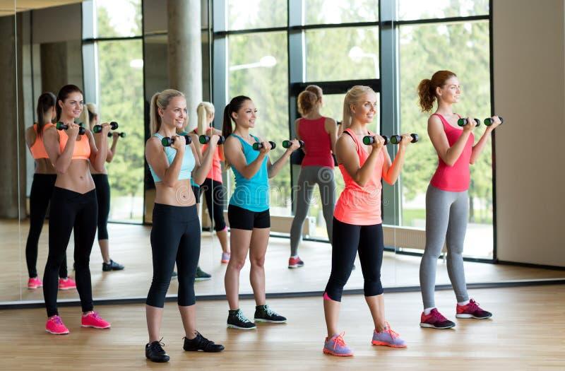Grupo de mulheres com pesos no gym imagens de stock