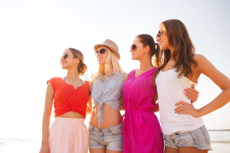 Grupo de mulheres de sorriso nos óculos de sol na praia fotografia de stock royalty free