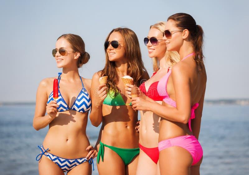 Grupo de mulheres de sorriso que comem o gelado na praia imagens de stock royalty free