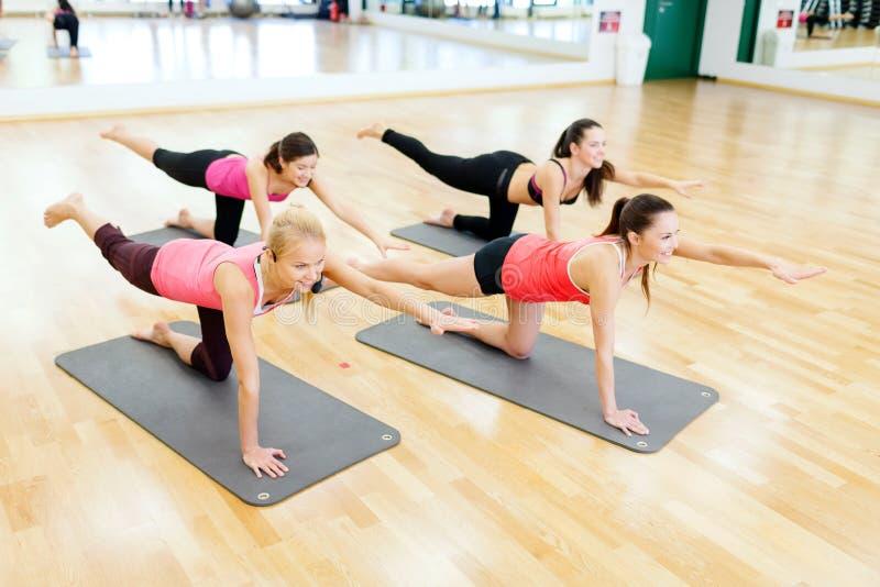 Grupo de mulheres de sorriso que esticam em esteiras no gym foto de stock royalty free