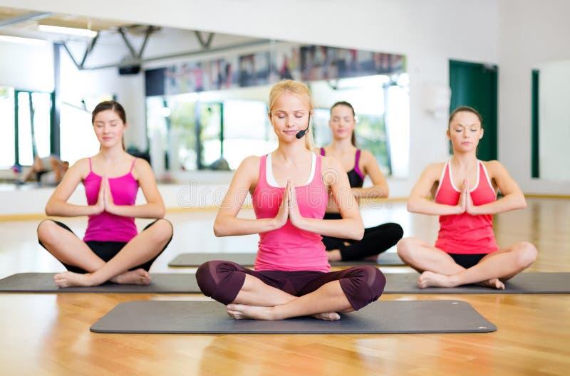 Grupo de mulheres de sorriso que meditam na pose da ioga imagem de stock royalty free