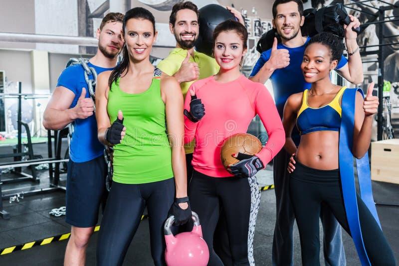 Grupo de mulheres e de homens no gym que levanta no treinamento da aptidão fotos de stock