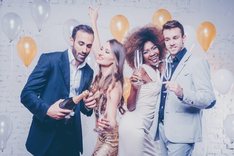 Grupo de mulheres e de homens que comemoram com champanhe fotografia de stock