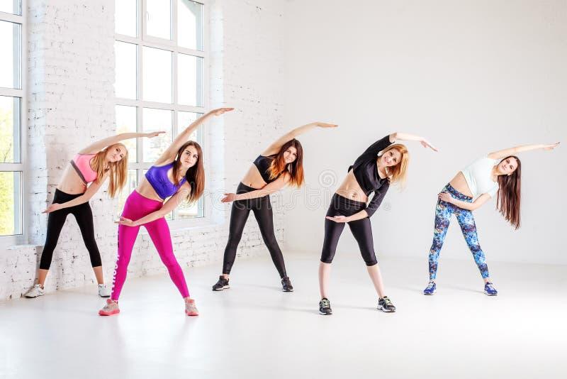 Grupo de mulheres envolvidas em carregar o gym O conceito do spor imagens de stock royalty free