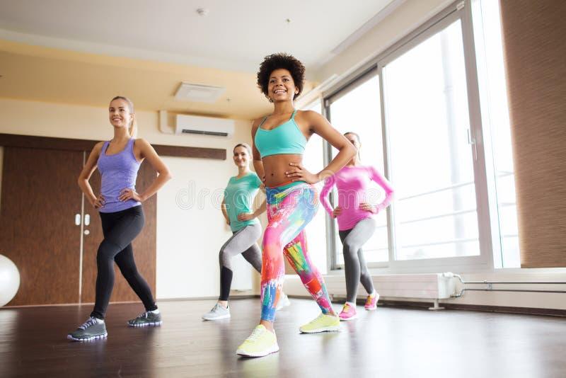 Grupo de mulheres felizes que dão certo no gym fotografia de stock
