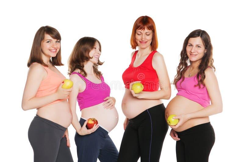 Grupo de mulheres gravidas felizes de sorriso com frutos fotografia de stock royalty free