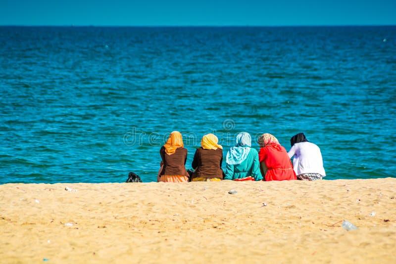 Grupo de mulheres marroquinas que sentam-se na praia fotos de stock royalty free