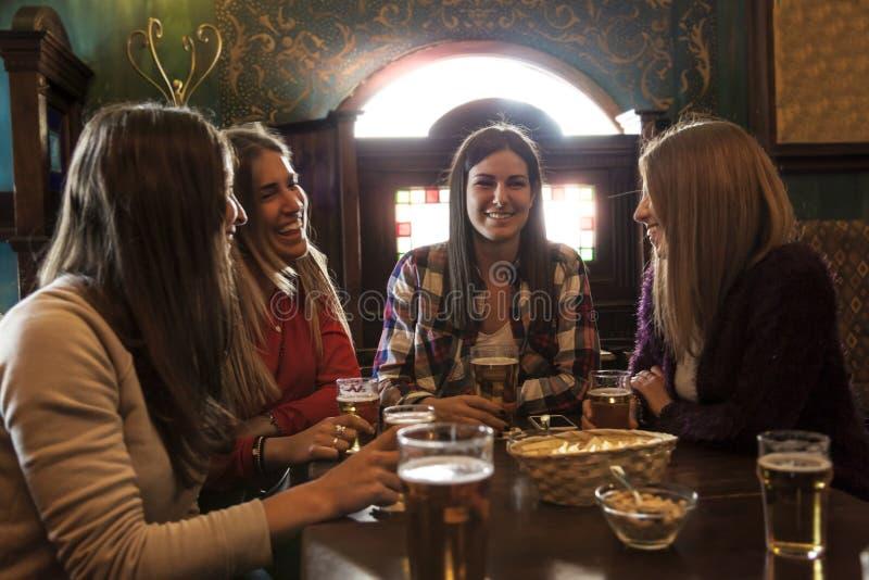 Grupo de mulheres milenares que comem a cerveja bebendo do divertimento foto de stock
