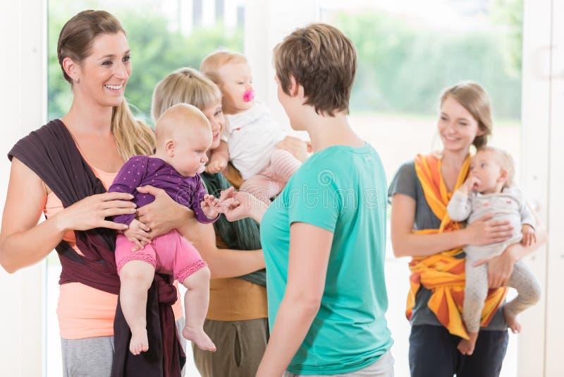 Grupo de mulheres que aprendem como usar estilingues do bebê para a mãe-criança fotos de stock royalty free