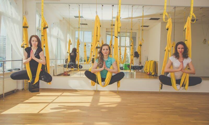 Grupo de mulheres que fazem a ioga da mosca nas redes fotos de stock royalty free