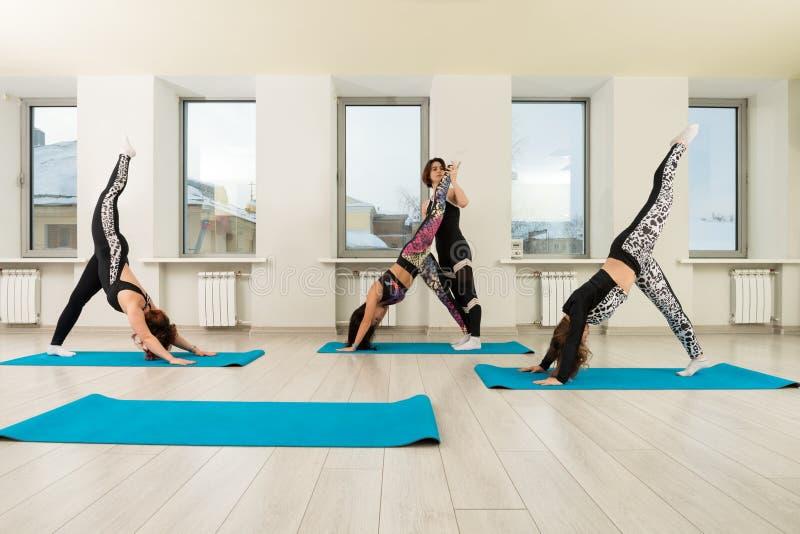 Grupo de mulheres que fazem a ioga em uma opinião do gym dos esportes imagens de stock