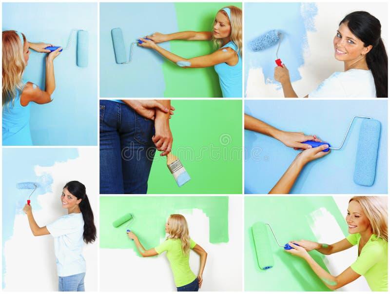 Grupo de mulheres que pintam uma parede foto de stock