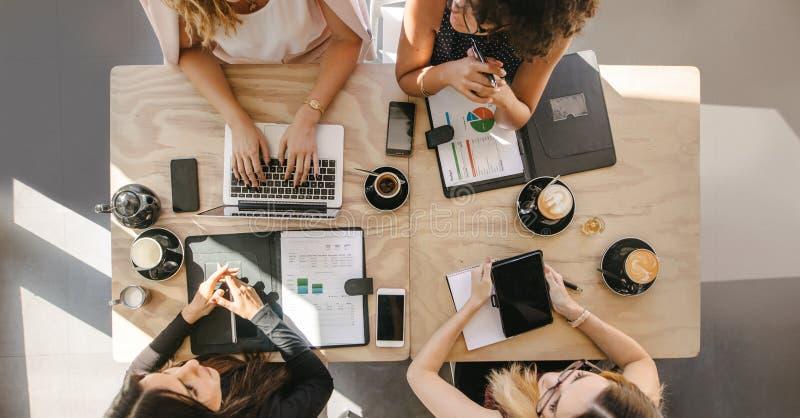 Grupo de mulheres que trabalham junto na cafetaria fotos de stock