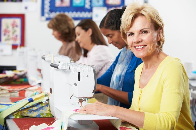 Grupo de mulheres que usam máquinas de costura elétricas na classe fotografia de stock