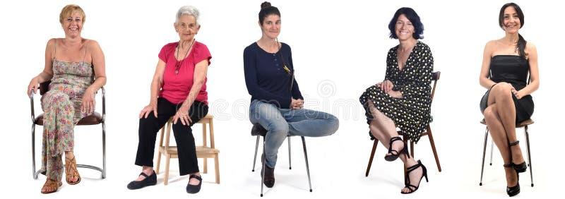 Grupo de mulheres sentadas em cadeira de fundo branca imagens de stock royalty free