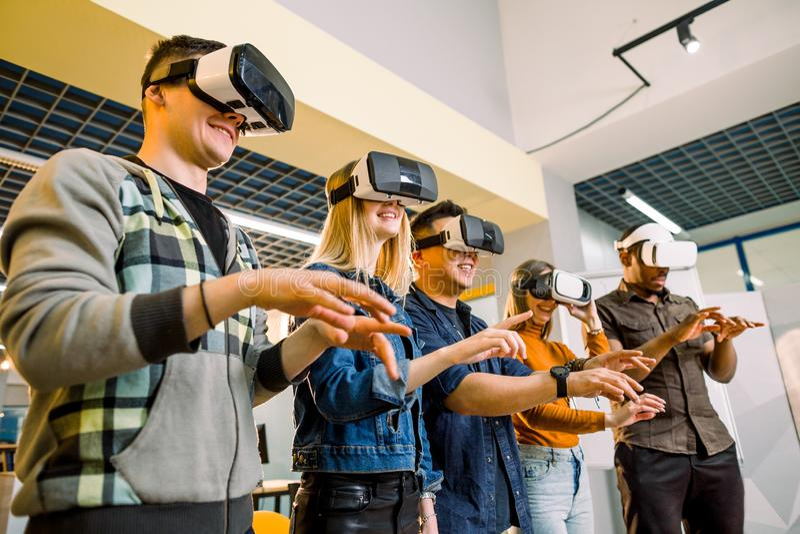 Grupo de Multiethnical de homens novos e de mulheres no vestuário desportivo com os óculos de proteção da realidade virtual Teste fotos de stock