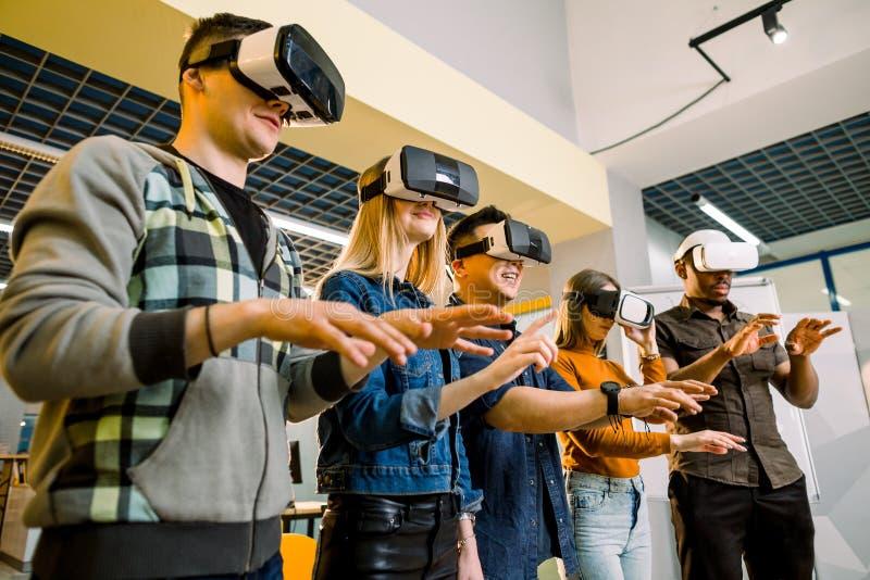 Grupo de Multiethnical de homens novos e de mulheres no vestuário desportivo com os óculos de proteção da realidade virtual Teste fotos de stock royalty free