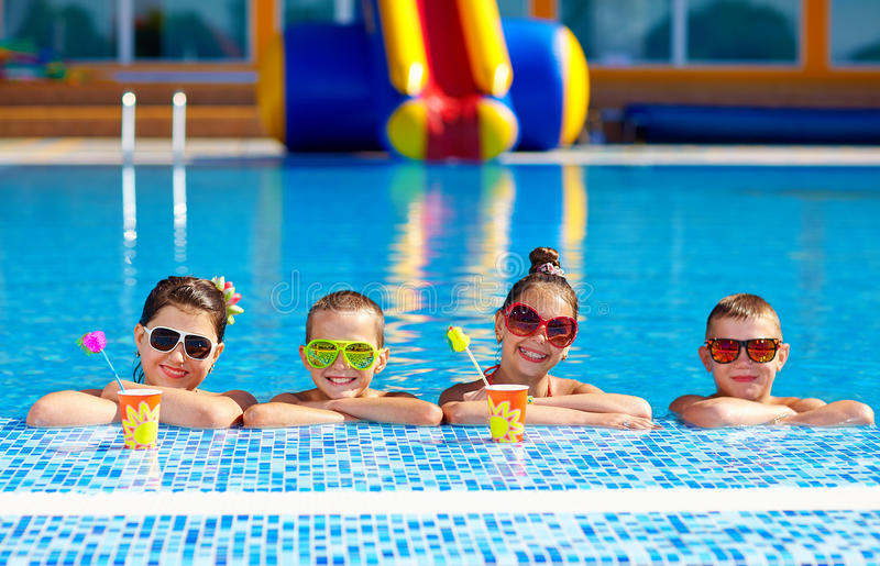 Grupo de niños adolescentes felices en la piscina foto de archivo