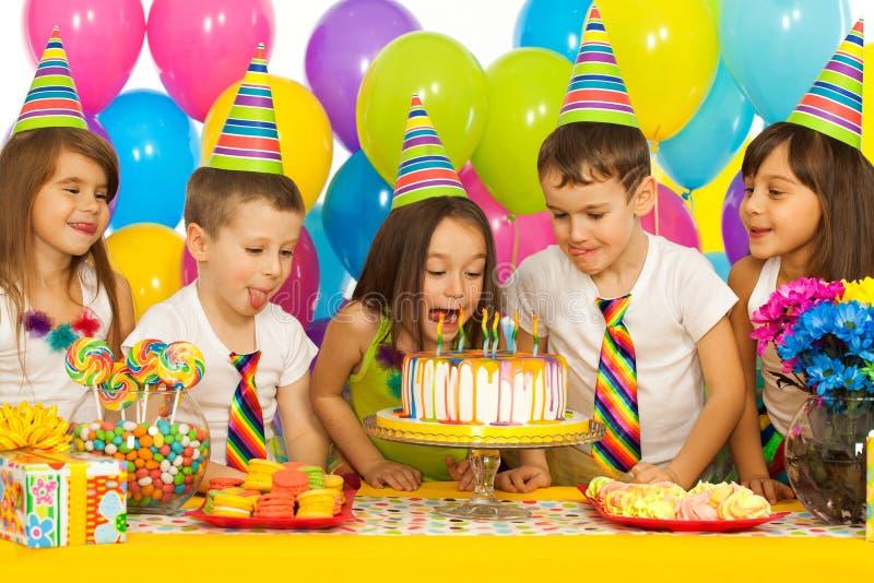 Grupo de niños alegres con la torta en el cumpleaños imágenes de archivo libres de regalías