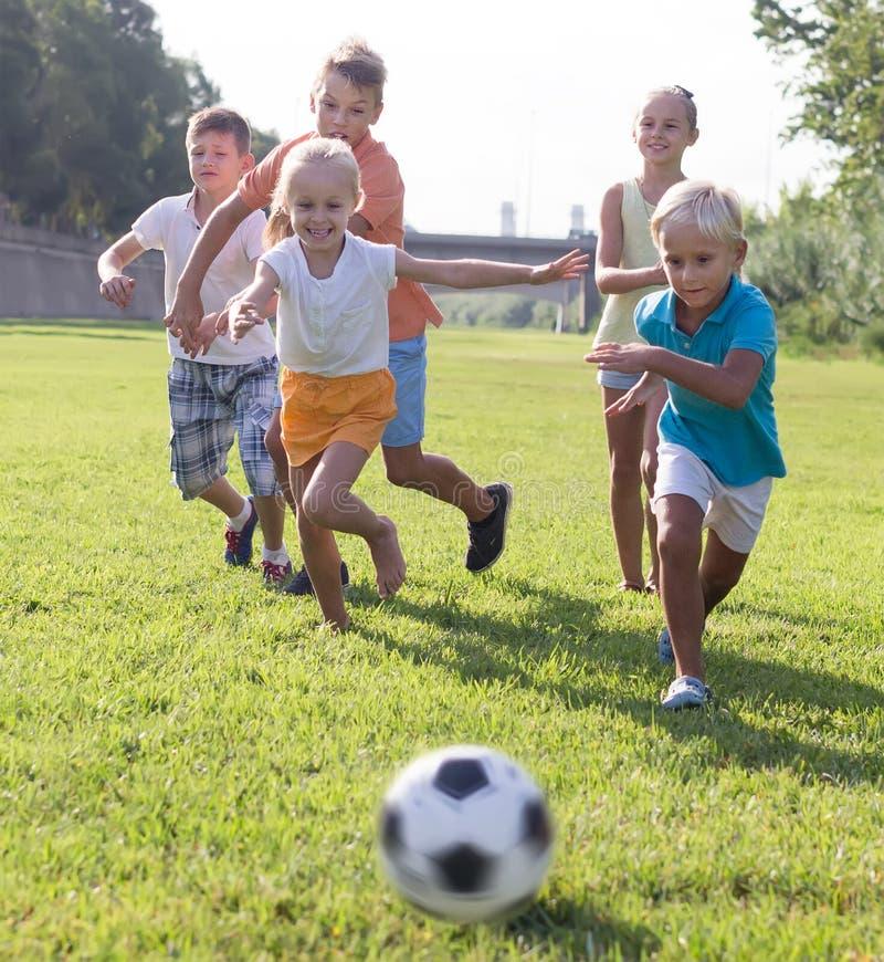 Grupo de niños alegres que juegan al fútbol junto en el césped verde i imagenes de archivo