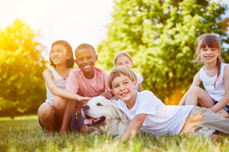Grupo de niños con el perro perdiguero de Golder imagenes de archivo