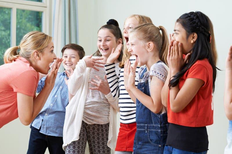 Grupo de niños con el profesor Enjoying Drama Class junto imagen de archivo