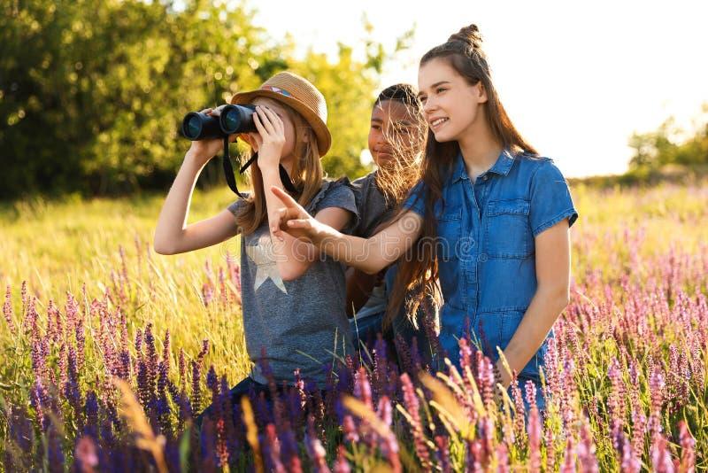 Grupo de niños con los prismáticos en campo imagenes de archivo