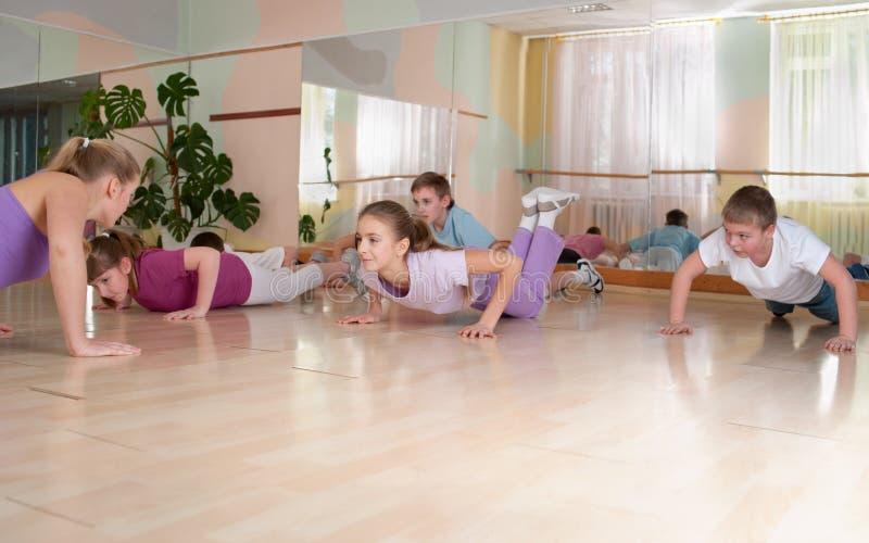 Grupo de niños contratados al entrenamiento físico. imagenes de archivo
