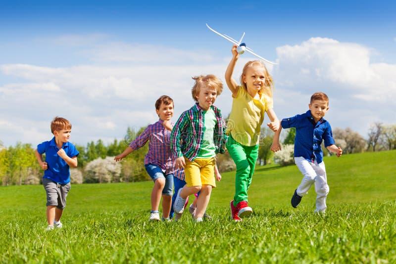 Grupo de niños corrientes felices con el aeroplano blanco imágenes de archivo libres de regalías