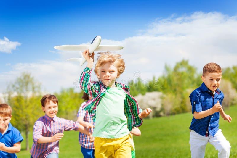 Grupo de niños corrientes felices con el juguete del aeroplano fotografía de archivo