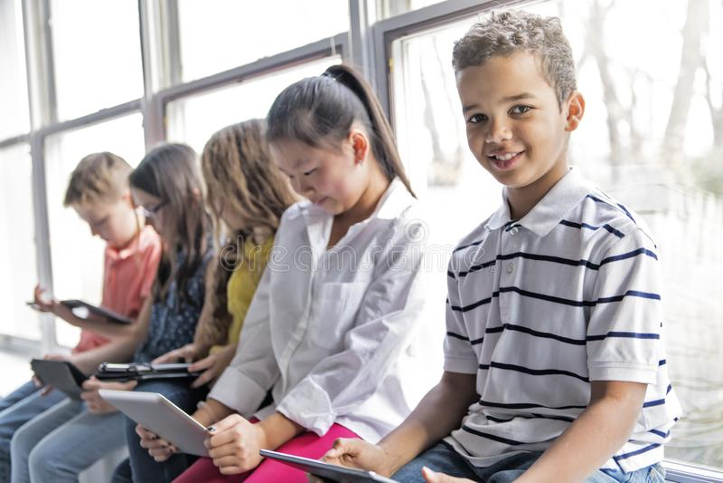 Grupo de niños curiosos que miran la materia en la pantalla de la tableta imagen de archivo libre de regalías