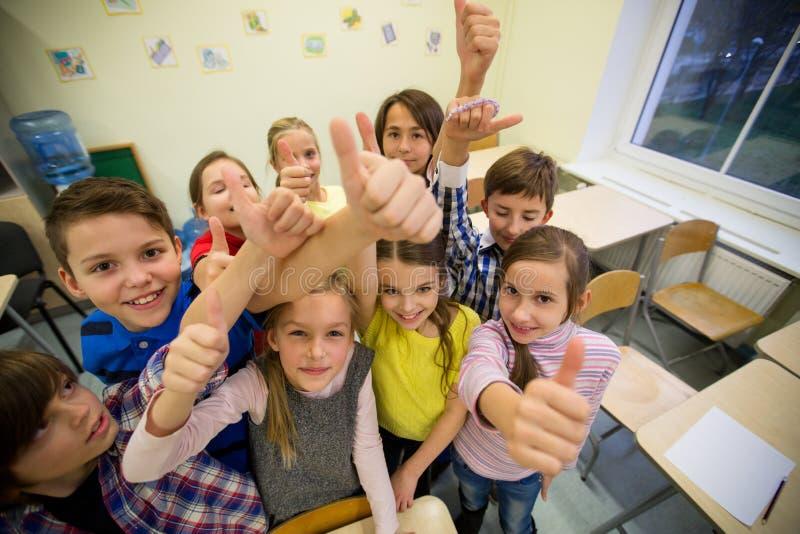 Grupo de niños de la escuela que muestran los pulgares para arriba imágenes de archivo libres de regalías
