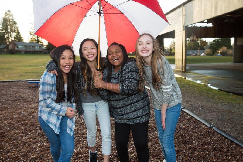 Grupo de niños debajo de un paraguas en la lluvia fotografía de archivo