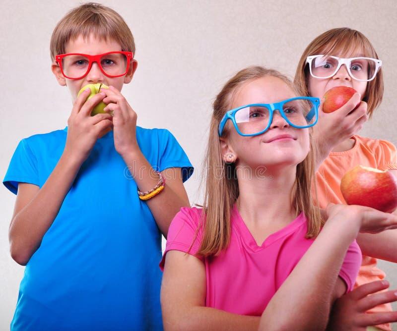 Grupo de niños divertidos con la presentación de las manzanas imagen de archivo