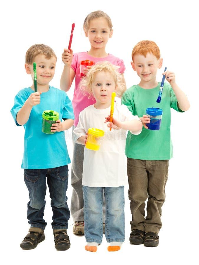 Grupo de niños felices con los cepillos de pintura de los cabritos fotografía de archivo libre de regalías
