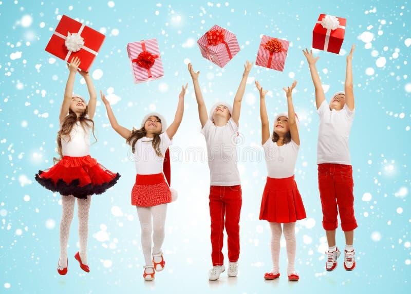 Grupo de niños felices en cajas de regalo de cogida del sombrero de la Navidad fotografía de archivo libre de regalías