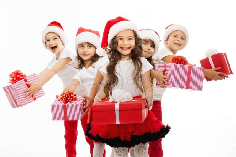Grupo de niños felices en sombrero de la Navidad con los presentes foto de archivo