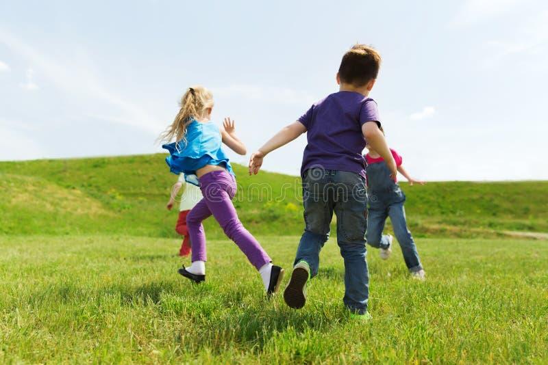 Grupo de niños felices que corren al aire libre imagen de archivo