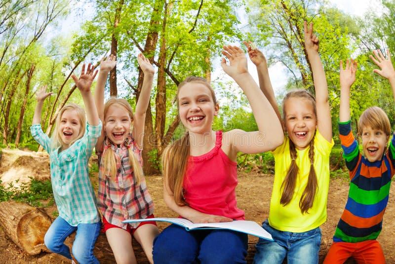 Grupo de niños felices que leen un libro en parque del verano fotos de archivo libres de regalías