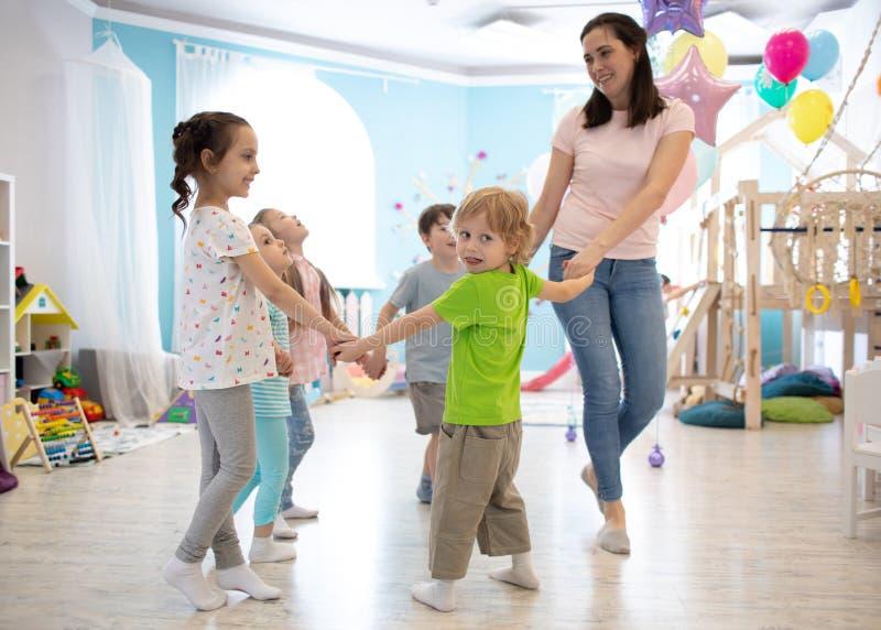 Grupo de niños felices que se colocan en el círculo que lleva a cabo las manos, jugando con su profesor en sala de clase fotografía de archivo libre de regalías