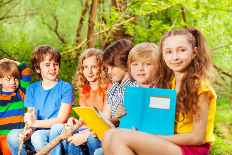 Grupo de niños felices que se sientan con los libros en el parque foto de archivo libre de regalías