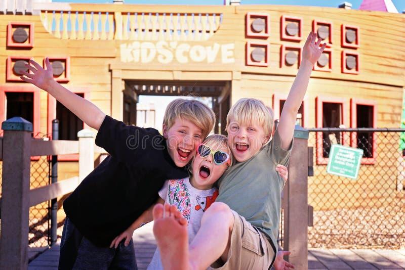 Grupo de niños felices, sonrientes afuera en el parque el día de verano fotografía de archivo