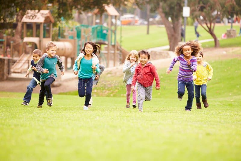 Grupo de niños jovenes que corren hacia cámara en parque fotografía de archivo