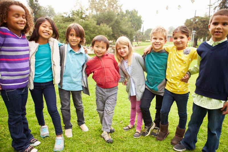 Grupo de niños jovenes que cuelgan hacia fuera en parque imagenes de archivo